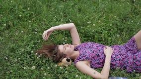 Adatti il ritratto di menzogne di modello della bella ragazza castana femminile sexy sull'erba nel parco stock footage