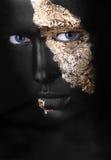 Adatti il ritratto di una ragazza dalla carnagione scura con trucco dell'oro Fronte di bellezza fotografia stock