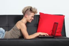 Adatti Internet di lettura rapida della donna in un computer portatile a casa Fotografie Stock
