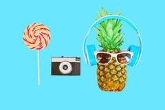 Adatti l'ananas con la macchina fotografica dell'annata delle cuffie e degli occhiali da sole Fotografia Stock