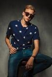 Adatti l'uomo che si siede sulla sedia con gli occhiali da sole sopra Immagini Stock Libere da Diritti