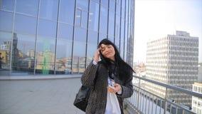 Adatti la bella donna di Latina del latino-americano che manda un sms sullo smartphone che cammina nella città video d archivio