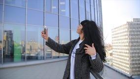 Adatti la bella donna di Latina del latino-americano che manda un sms sullo smartphone nel caffè bevente del latte della città stock footage