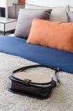 Adatti la borsa della femmina in camera da letto moderna con i cuscini variopinti sopra Immagine Stock