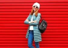Adatti la donna abbastanza sorridente con lo zaino su un fondo rosso Fotografie Stock Libere da Diritti