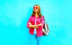 Adatti la donna abbastanza sorridente in rivestimento rosa del denim su un blu Fotografie Stock Libere da Diritti