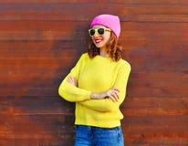 Adatti la donna abbastanza sorridente in vestiti variopinti sopra fondo di legno che porta il maglione rosa di giallo del cappell Fotografia Stock Libera da Diritti