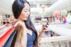 Adatti la donna asiatica con la borsa facendo uso del telefono cellulare, centro commerciale Immagine Stock Libera da Diritti