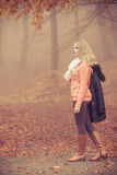 Adatti la donna bionda con il rivestimento nel parco di autunno Fotografie Stock Libere da Diritti
