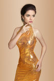 Adatti la donna castana elegante in vestito dorato isolato su beige Fotografie Stock Libere da Diritti