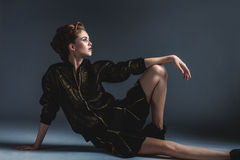 Adatti la donna che si siede sul pavimento in una posa elegante fotografia stock libera da diritti