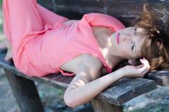 Adatti la donna che si trova sul banco, con un indumento rosa del pezzo fotografia stock libera da diritti