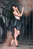 Adatti la donna con le gambe lunghe in scarpe nere del tacco alto e breve gonna di cuoio Fotografie Stock Libere da Diritti
