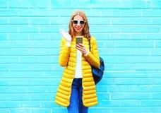 Adatti la donna di risata che per mezzo dello smartphone su un mattone blu Immagini Stock Libere da Diritti