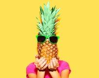 Adatti la donna e l'ananas del ritratto con gli occhiali da sole sopra giallo variopinto Fotografie Stock Libere da Diritti