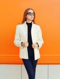 Adatti la donna graziosa che porta un rivestimento delle camice contro l'arancia Fotografie Stock