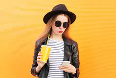 Adatti la donna graziosa che utilizza lo smartphone nello stile del nero della roccia sopra l'arancia Fotografia Stock Libera da Diritti