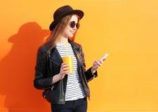 Adatti la donna graziosa che utilizza lo smartphone nello stile del nero della roccia sopra l'arancia variopinta Immagini Stock