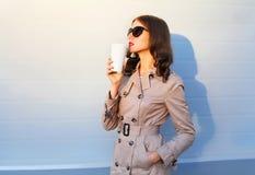 Adatti la donna graziosa con la tazza di caffè che gode del gusto che cammina nella sera della città fotografia stock
