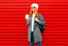 Adatti la donna graziosa con la tazza di caffè che porta un cappotto, zaino su un fondo rosso Fotografia Stock