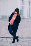 Adatti la donna incinta che ha una passeggiata sulla via Immagini Stock