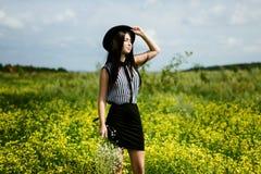 Adatti la donna nella condizione black hat sul giacimento di fiori soleggiato giallo Immagine Stock