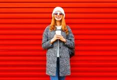 Adatti la donna sorridente con la tazza di caffè che porta un cappotto su un rosso Fotografia Stock Libera da Diritti