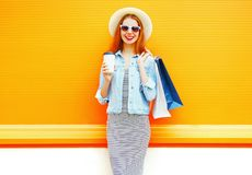 Adatti la donna sorridente con una tazza di caffè, i sacchetti della spesa, cappello di paglia Fotografie Stock