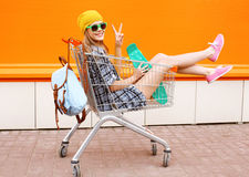 Adatti la donna sorridente dei pantaloni a vita bassa divertendosi l'uso occhiali da sole immagine stock libera da diritti