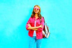 Adatti la donna sorridente in rivestimento rosa del denim su backgroun blu Immagini Stock
