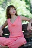 Adatti la donna sul banco, con un indumento rosa del pezzo immagine stock
