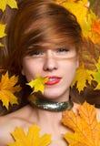 Adatti la foglia di acero sorridente di giallo di autunno della tenuta della donna di stile dentro Fotografie Stock