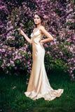 Adatti la foto di bella donna che posa fra gli alberi di fioritura della molla Immagine Stock