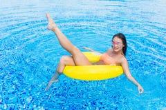 Adatti la foto di bella ragazza sexy nella cima gialla e degli occhiali da sole che si rilassano il galleggiamento sull'anello go fotografia stock libera da diritti