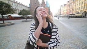 Adatti la giovane donna che cammina e che parla sul telefono cellulare in una via della città, in un taccuino della tenuta della  stock footage
