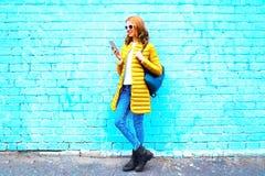 Adatti la giovane donna che per mezzo dello smartphone sul fondo blu del mattone Fotografia Stock Libera da Diritti