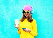 Adatti la musica d'ascolto della donna spensierata abbastanza dolce in cuffie che passano in rassegna facendo uso dello smartphon Immagine Stock Libera da Diritti