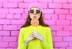 Adatti la ragazza abbastanza fresca del ritratto con la lecca-lecca sopra il rosa variopinto Fotografie Stock