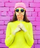 Adatti la ragazza abbastanza fresca del ritratto divertendosi con la lecca-lecca sopra il rosa Fotografia Stock Libera da Diritti