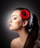 Adatti la ragazza castana con il fiore isolato su fondo strutturato Fotografie Stock