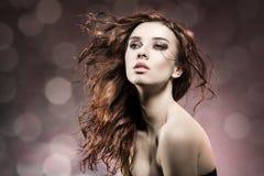 Adatti la ragazza con i capelli di volo sul fondo del chiarore Immagine Stock
