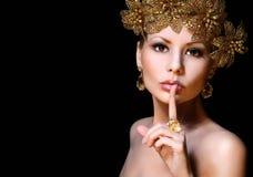 Adatti la ragazza con i gioielli dell'oro sopra fondo nero. Bellezza immagine stock libera da diritti