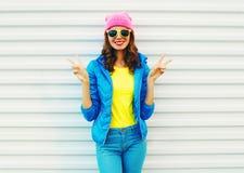 Adatti la ragazza sorridente abbastanza fresca in vestiti variopinti divertendosi sopra il fondo bianco gli occhiali da sole rosa Fotografia Stock Libera da Diritti