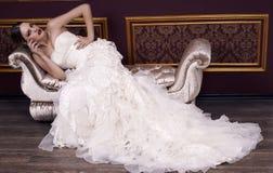 Adatti la sposa con capelli biondi in vestito lussuoso che posa nell'interno Fotografia Stock