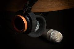 Adatti le cuffie su un microfono di legno dello studio e del supporto su un fondo nero fotografia stock libera da diritti
