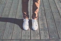 Adatti a pantaloni a vita bassa l'uomo fresco con le scarpe da tennis bianche, annata molle tonificata Immagini Stock