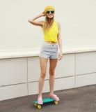Adatti a pantaloni a vita bassa l'uso sorridente fresco della ragazza occhiali da sole Immagini Stock