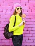 Adatti a ritratto la ragazza graziosa con la lecca-lecca sopra variopinto rosa Fotografie Stock