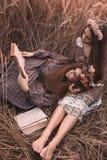 Adatti un ritratto di due belle ragazze all'abbigliamento disegnato boho d'uso del campo del tramonto Fotografia Stock