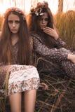 Adatti un ritratto di due belle ragazze all'abbigliamento disegnato boho d'uso del campo del tramonto Immagini Stock